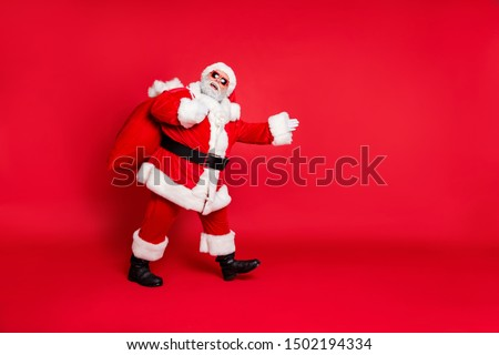 Side profile view photo of cheerful delightful overweight big abdomen grandfather in boots belt fur making steps showing way hand holding huge sack full of interesting surprises isolated background