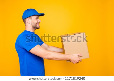 Side profile view portrait of handsome attractive cheerful bearded deliver with stubble in blue uniform handling card-board box, isolated over bright vivid yellow background