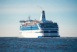 Side rear view of large modern cruise ship of ferry sailing in blue sea.