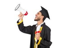 Side shot of a young man Cheerful young man wearing the graduation robe and holding his certificate and megaphone make an announcement that he graduate, isolated on white background