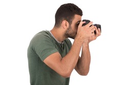 Side shot of handsome young photographer taking a photo, guy wearing green t-shirt and black pants, isolated on white background