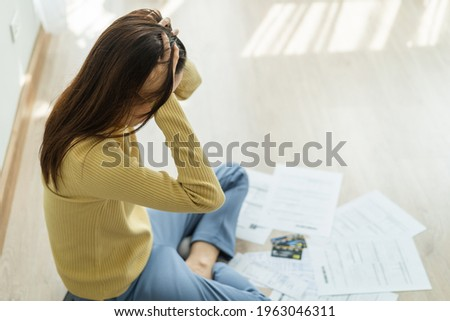 Side, Top view owe asian woman, female sitting on floor home stressed and confused by calculate expense from invoice or bill, no money to pay, mortgage or loan. Debt, bankruptcy or bankrupt concept. Stockfoto ©