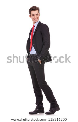 side vie of a young business man standing with his hands in pockets and looking to his back on white background