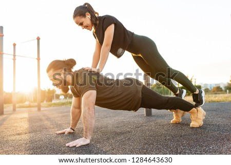 Side view - a strong and enduring young male weightlifter with his sports girlfriend doing pushups with her on his back on the playground on a summer evening. Sport and endurance concept