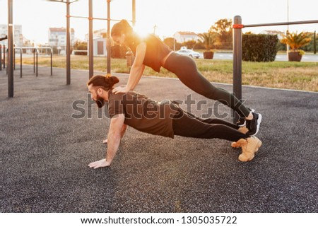 Side view - a strong and enduring young male weightlifter with his sports girlfriend doing pushups with her on his back on the playground on a summer evening. Sport and endurance concept #1305035722
