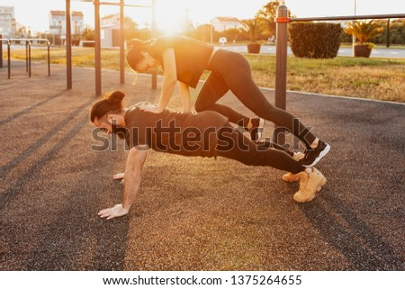 Side view - a strong and enduring young male weightlifter with his sports girlfriend doing pushups with her on his back on the playground on a summer evening. Sport and endurance concept #1375264655