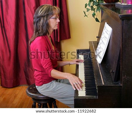 side view a women in red playing an upright piano