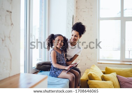 Side view African American cute joyful child with curly pigtails browsing tablet looking at camera and sitting with cheerful young mother on blanket covered sill in room