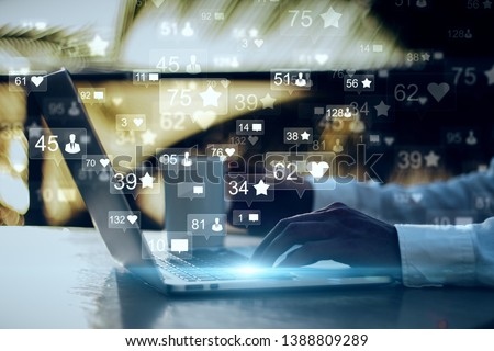 Side view and close up of businessman hands using laptop with social media icons on blurry outdoor background. Communication and network concept. Double exposure