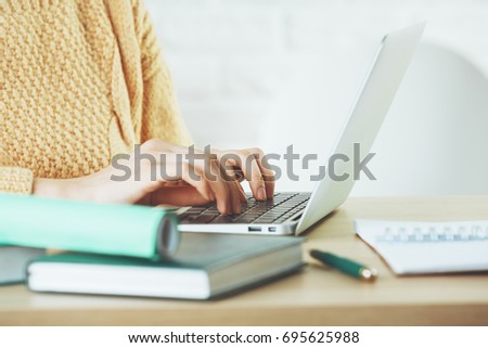 Side view and close up of woman hands typing on laptop keyboard placed on wooden office desktop with supplies. Technology concept