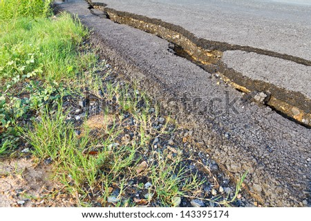 Side view asphalt road broken due to collapsing ground until the grass grows.