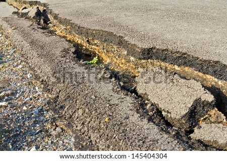 Side view asphalt road broken due to collapsing ground until the grass grows