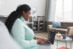 Side view at curvy African American woman using laptop while working from home sitting on couch in minimal interior, copy space