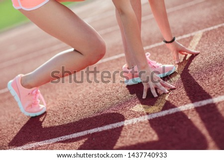 side view Athletic woman in pink shorts and tank tops on running track getting ready to start run, Amateur athlete. Close-up legs and arms.