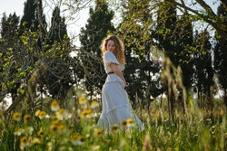 Side view beautiful young female wearing maxi summer dress standing on verdant blooming meadow in sunny countryside