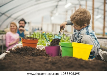 Side view boy filling pink flower pot with soil. Blond kid playing with gardening tools in greenhouse. Happy, active childhood. #1083606395