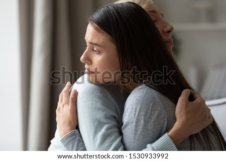 Side view caring middle aged woman embracing comforting soothing sad millennial daughter, demonstrating support and love. Upset worried young lady cuddling hugging empathic loving older mother.