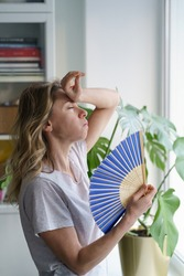 Side view caucasian tired overheated woman in t-shirt using wave fan suffer from heat sweating, cools herself, closed eyes feels sluggish due problem no air conditioner at home at summer weather.