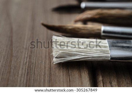 Side view close up of a variety of artist\'s paintbrushes, laid out in a row on a wood plank table.