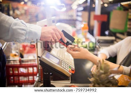 Side view close up of unrecognizable customer handing credit card to cashier paying via bank terminal at grocery store #759734992