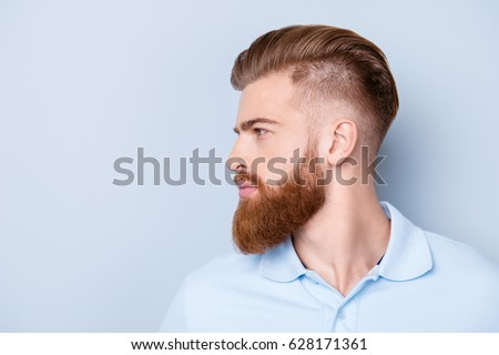 Side view close up portrait of handsome bearded young serious man in polo isolated on copyspace