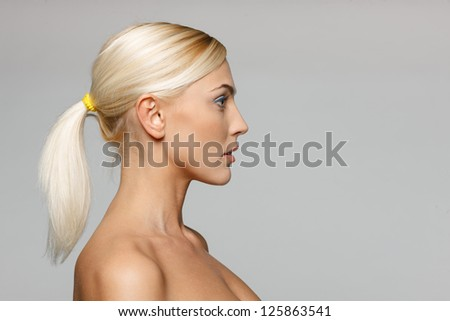 Side view closeup of beautiful blond woman looking forward over gray background