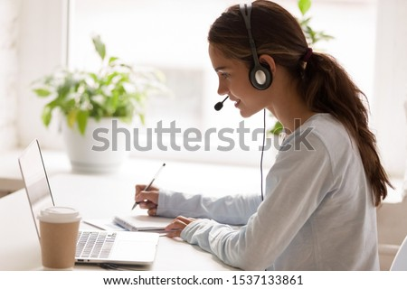 Side view concentrated millennial mixed race woman wearing headset with microphone, looking at laptop screen, listening educational webinar, taking notes, getting remote online education at home.