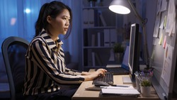 side view confident asian woman manager working overtime late at home is receiving a mail from her colleague on desktop computer