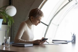 Side view confident serious 30s short haired female notary reading paper business agreement, checking newest law in mobile phone application, concentrated editor working on handwritten documents.