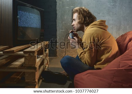 Side view excited bearded man playing in video game while sitting on armchair in room. Entertainment concept