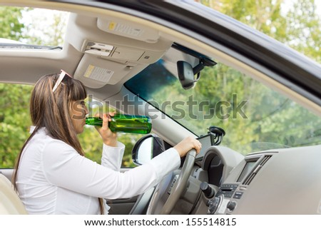 Side view from inside the vehicle of an alcoholic woman driver drinking and driving her car posing a threat to the safety of other motorists