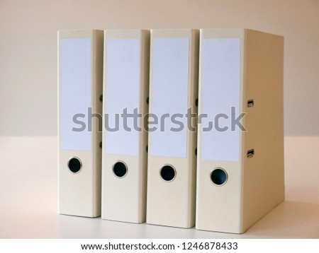 Side view from the right towards a collection of four binders folders for office paper standing on a clean white table in office environment