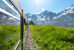 Side view from window of modern electric green and yellow tourist train of the Wengernalpbahn rack railway from Lauterbrunnen to Kleine Scheidegg near Kleine Scheidegg railway, Switzerland