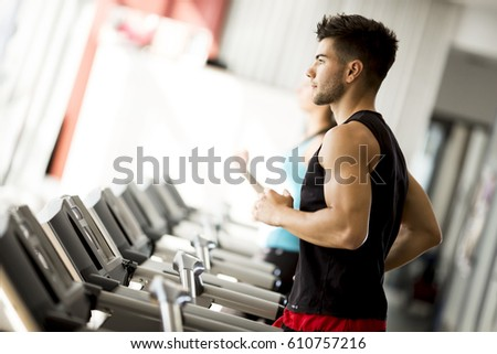 Side view full length of young man in sportswear running on treadmill at gym