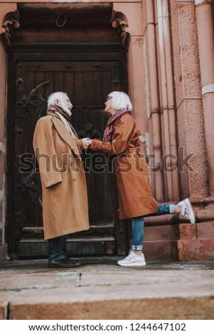 Side view full length portrait of old bearded gentleman and his wife standing near door of old building. They looking at each other and smiling
