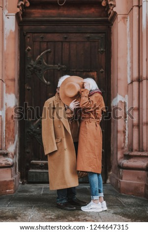 Side view full length portrait of old gentleman and his wife hiding behind female headwear while standing near door of old building