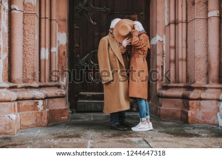 Side view full length portrait of old gentleman and his wife hiding behind headwear while standing near old building
