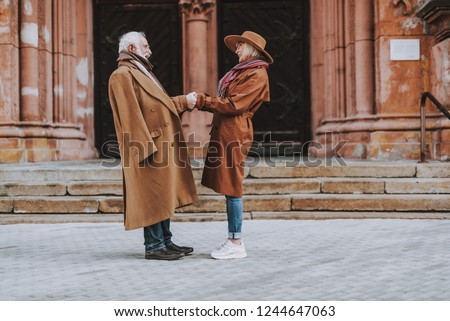 Side view full length portrait of stylish bearded man and his wife standing near old building. They looking at each other and smiling