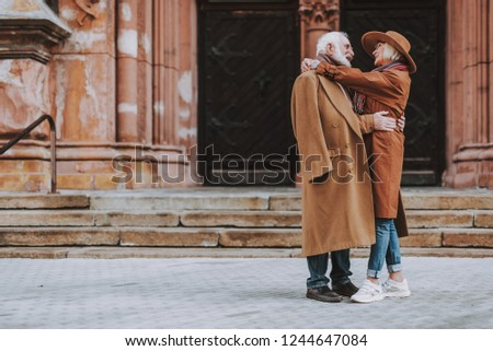 Side view full length portrait of stylish bearded man embracing his wife while standing near old building. They looking at each other and smiling