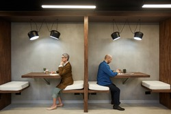 Side view full length portrait of two adult people separated by wall while sitting in separate cafe booths, copy space