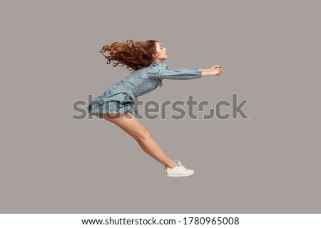 Side view girl rushing at full speed accelerate, steering driving fast and levitating in air. Model flying rapidly with hurricane wind blowing extremely sharply. indoor studio shot isolated on gray Сток-фото ©