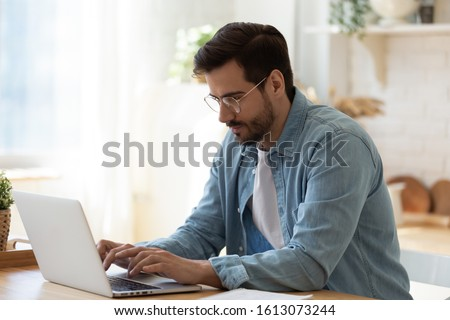 Photo of Side view handsome young businessman in eyewear working with computer remotely, sitting at wooden table in kitchen. Pleasant happy man communicating in social network, searching information online.