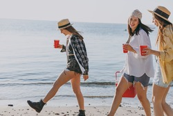 Side view happy female friends young women 20s in straw hat summer clothes hang out together carry food in picnic refrigerator glasses outdoor on sea beach background People vacation journey concept