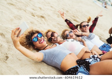 Side view. Happy girlfriends taking selfies lying on sand. Smiling happily. Cool trendy summer outfit.