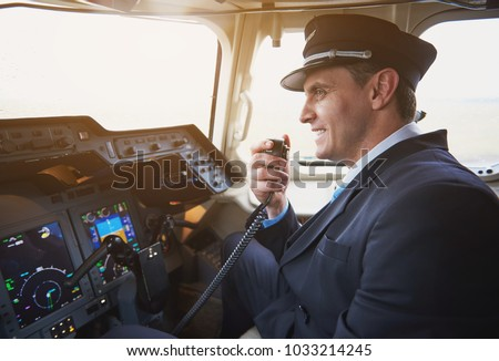 Side view happy pilot talking by portable radio set in cabin of airplane. Conversation and occupation concept