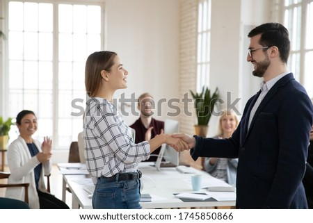 Side view happy young female worker shaking hands with smiling confident boss in eyewear. Satisfied with good job results team leader praising employee at meeting while diverse coworkers applauding.