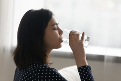 Side view happy young multiracial asian korean woman drinking cool distilled water from glass, keeping dietary lifestyle, enjoying morning healthcare habit, hydrating organism with fresh aqua at home.