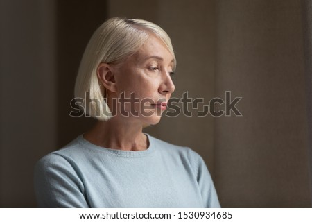 Side view head shot close up portrait sad upset mature lost in thoughts lady feeling lonely. Stressed pensive older woman thinking about health problems, bad diagnosis, family troubles, looking away.