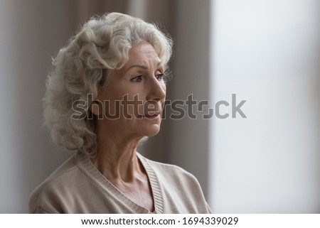 Side view head shot close up worried unhappy middle aged senior woman looking at window, suffering from loneliness at home, thinking of health mental psychological problems alone at nursing housse.