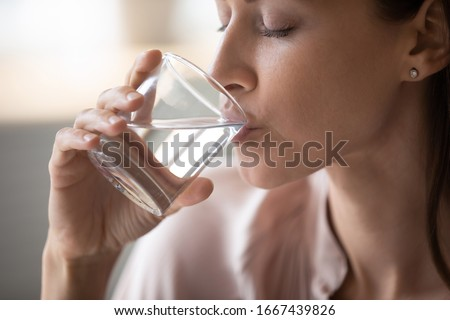 Side view head shot close up young woman drinking pure still water in morning. Healthy thirsty lady enjoying healthy lifestyle daily habit, natural beauty, perfect skin body care aqua balance concept.